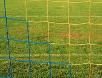 横渡的足球网,在目标网的足球橄榄球与在橄榄球操场的塑料草 库存图片
