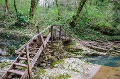 横渡蓝色山小河的老木桥 免版税库存图片