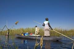 横渡通过使用Mokoro小船的三角洲 图库摄影