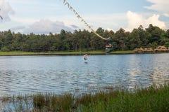 横渡邮编线的年轻人一个湖在清迈 库存图片