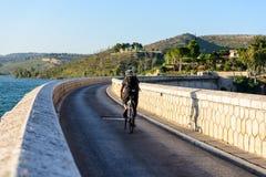 横渡马拉松水坝的骑自行车者 库存照片