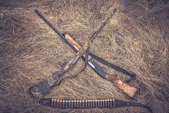 横渡寻找有弹药传送带的猎枪在干草的减速火箭的葡萄酒样式当狩猎背景 免版税库存照片