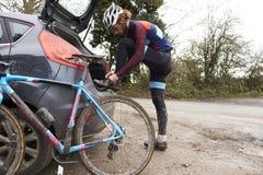 横越全国的骑自行车者乘他的汽车,改变在自行车乘驾以后 免版税库存照片