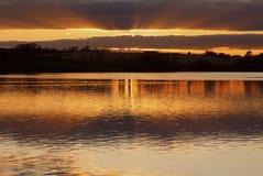 横跨一个闪烁雷文斯索普水库被反射的黄褐色的日落,雷文斯索普,北安普敦郡 库存图片
