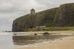 横跨下坡海滩的一个看法在伦敦德里郡在有一个火车标题的北爱尔兰往峭壁隧道 库存图片