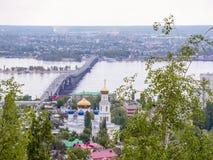 横跨伏尔加河的路桥梁在市萨拉托夫和恩格斯之间 城市` s地平线 假定大教堂教会kogalym正统俄国西伯利亚城镇处女西部 可以 免版税图库摄影