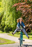 横跨公园的无忧无虑的少年骑马自行车 免版税库存照片