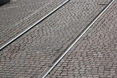 横跨圆石铺砌路面的老轨道 免版税图库摄影