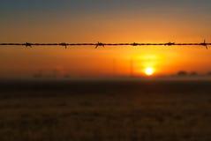 横跨太阳现出轮廓的领域的铁丝网 免版税库存图片