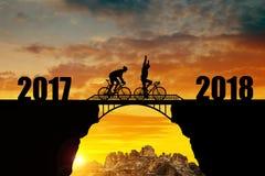 横跨桥梁的骑自行车者骑马到新年里2018年 库存照片