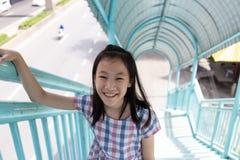 横跨步行天桥的亚洲逗人喜爱的女孩步行,安全的c 免版税库存照片