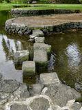 横跨水的垫脚石道路在日本庭院里 库存照片