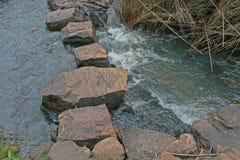 横跨流动的水的垫脚石 图库摄影