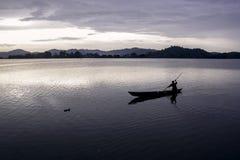 横跨湖的亚洲渔夫划船 免版税库存图片