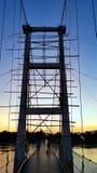 横跨砰河的Underconstruction吊桥在五颜六色的暮色天空期间 来兴府,泰国 图库摄影