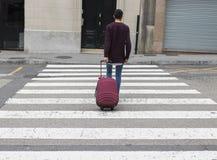 横跨街道的人带着手提箱 免版税库存图片
