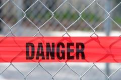 横跨链节篱芭的红色反射性危险障碍磁带 库存图片