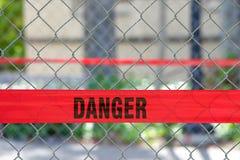 横跨链节篱芭的红色反射性危险障碍磁带 免版税库存图片