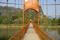 横跨Nam歌曲河的步行桥游人的安置了Vang Vieng,老挝镇  免版税库存图片
