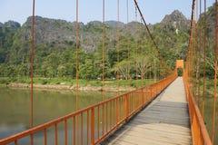 横跨Nam歌曲河的步行桥游人的安置了Vang Vieng,老挝镇  免版税图库摄影
