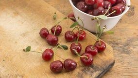 樱桃在木砧板和在碗 免版税库存图片