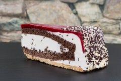 樱桃在黑暗的板岩的奶油奶油蛋糕片断与一个石墙 库存照片