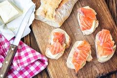 樱桃手抓食物无盐干酪蕃茄 开胃菜与长方形宝石、三文鱼和黄油的点心三明治在木背景的土气木板 顶视图, 库存图片