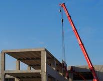 樱桃捡取器和一台望远镜起重机在工作在建筑大厦 库存照片