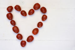 樱桃李子在白色木背景的快餐蕃茄 免版税库存图片