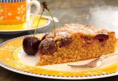 樱桃杏仁蛋糕用在明亮的板材的新鲜的樱桃 库存照片