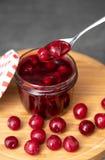 樱桃果酱,果酱匙子用在瓶子的莓果 一个瓶子与一个开放红色和白色盒盖的果酱在一个木板,一个委员会与 免版税库存照片