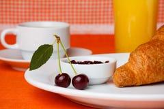 樱桃用汁液和新月形面包 免版税库存图片