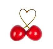 从樱桃的心脏形状与绿色叶子 免版税库存照片