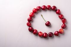 樱桃莓果圈子用与词根的一棵樱桃在木白色背景和水下落顶视图的中心宏观纹理 库存照片