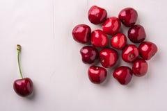 樱桃莓果用与词根宏观纹理的一棵樱桃在木白色背景和水下落顶视图 免版税库存照片