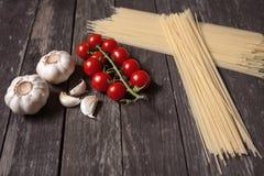 樱桃蕃茄,意粉面团,大蒜,在木选项 免版税库存照片