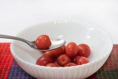 樱桃蜜饯在一棵碗和樱桃的在匙子 免版税图库摄影