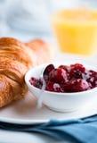 樱桃酸新月形面包的果酱 免版税库存图片
