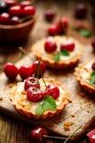 樱桃馅饼用香草乳蛋糕和焦糖,在一张木桌上的可口点心 图库摄影