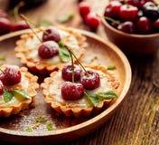 樱桃馅饼用香草乳蛋糕和焦糖,在一张木桌上的可口点心 免版税库存图片