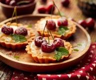 樱桃馅饼用香草乳蛋糕和焦糖,在一张木桌上的可口点心 库存图片