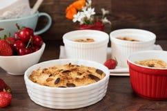 樱桃,草莓在白色碗的碎屑点心 樱桃,草莓,后边花 黑暗的木背景,顶视图 库存图片