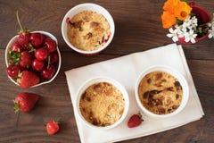 樱桃,草莓在白色碗的碎屑点心 樱桃,草莓,后边花 黑暗的木背景,顶视图 免版税库存图片