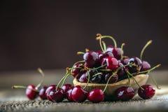 樱桃 樱桃新鲜的甜点 可口樱桃用水在老橡木桌上的减速火箭的碗滴下 免版税图库摄影