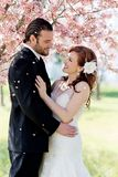 樱花瓣淋浴的新娘夫妇 免版税库存照片