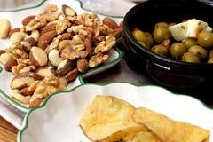 橄榄、希腊白软干酪、油炸马铃薯片、核桃、杏仁、腰果、巴西坚果和榛子服务用开胃酒 库存图片
