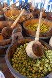 橄榄和辣子在木大桶在市场上 免版税库存照片