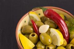绿橄榄开胃小菜用卤汁泡用柠檬和大蒜 免版税库存照片
