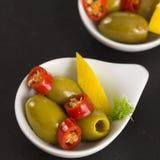 绿橄榄开胃小菜用卤汁泡用柠檬和大蒜 免版税库存图片
