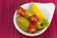 绿橄榄开胃小菜用卤汁泡用柠檬和大蒜 图库摄影